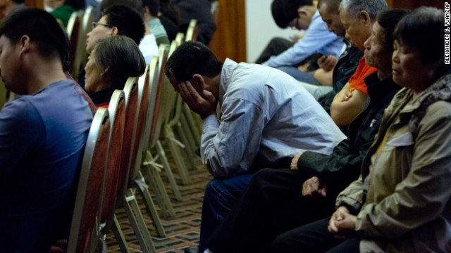 Relatives of Chinese passengers who were on Malaysia Airlines Flight 370 listen to part of the audio communications between Flight 370's cockpit and air traffic controllers during a meeting with Malaysian officials Wednesday, April 30, in Beijing.