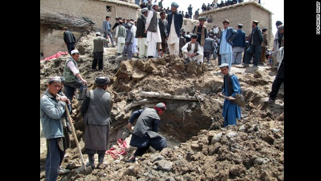 Residents dig through debris of collapsed houses in search of victims.