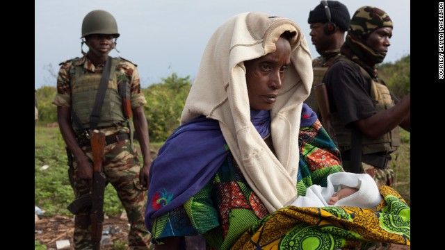 A woman holds one of the newborn babies near Kaga Bandoro as the convoy prepares to leave on April 29.