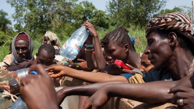 Despite security risks, refugees break away from the group to collect water from a nearby well, after the convoy ran out on the third day of the journey.