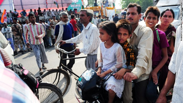 A family on a motorcycle passes Indian National Congress supporters in Varanasi on May 10.