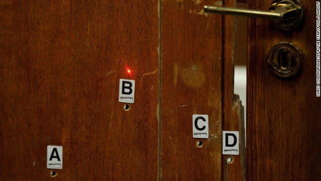A red laser dot points at bullet holes in the bathroom door for a forensic demonstration during the trial on May 12. Pistorius admits firing four bullets through the closed door, kil