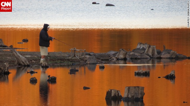 A fisherman casts his line into a lake reflecting the colors of fall in the Cohasset Reservoir of Wompatuck State Park in Hingham, Massachusetts. iReporter <a href='http://ireport.cnn.com/docs/DOC-863347'>Debra Roffo</a> considers herself lucky to live near such a beautiful place.