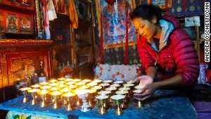 Ang Tshiring\'s daughter, Nima, attends to butter lamps in the prayer room.
