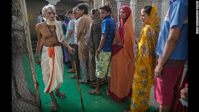 A Hindu holy man passes a line of people after voting at a polling station Monday, May 12, in Varanasi during the ninth and final phase of elections.