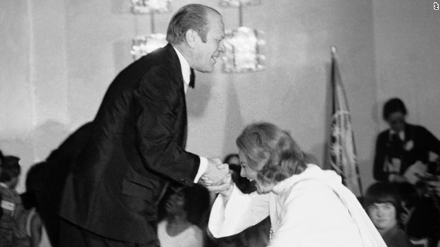 President Gerald Ford gives Walters a helping hand as she slips while stepping onto the stage in Washington during an awards presentation on March 10, 1975, for participants in the Special Olympics.
