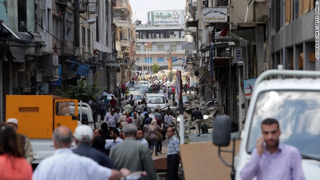 People pack the streets of Homs on May 12, days after the last rebel holdouts left the city.