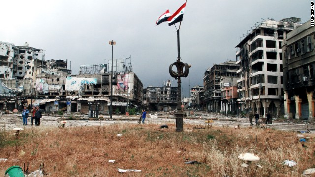 Two Syrian national flags fly overhead as government officials inspect the streets of war-torn Homs on Thursday, May 8, after the rebels withdrew from their remaining strongholds in the heart of the city.