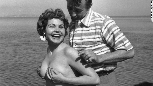 Starlet Simone Silva poses topless with idol Robert Mitchum in 1954.