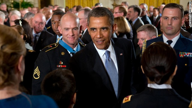 "Army Staff Sgt. Ty M. Carter, left, watches as President Obama greets family members of fallen service members after Carter was awarded the Medal of Honor during a White House ceremony on August 26, 2013. Carter was cited for his actions during the October 3, 2009, defense of Command Outpost Keating in Afghanistan, including ""running through a hail of enemy rocket propelled grenade and machine gun fire to rescue a critically wounded comrade."""