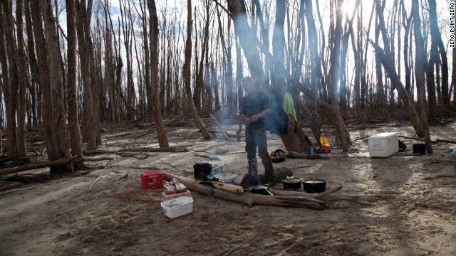 Bourdain cooks lunch over a driftwood fire on a sandbar along the Mississippi River.