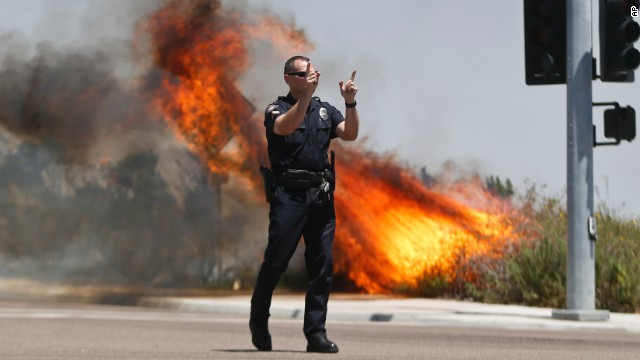 A Carlsbad police officer turns traffic away as flames rage behind him on May 14.