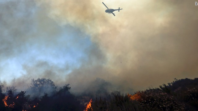 A helicopter flies over burning vegetation near homes in Carlsbad on May 14.