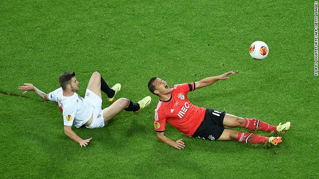 Benfica's Brazilian forward Lima (right) is brought down by Sevilla's defender Alberto Moreno inside the box on a tense night when both sides had penalty appeals turned down.