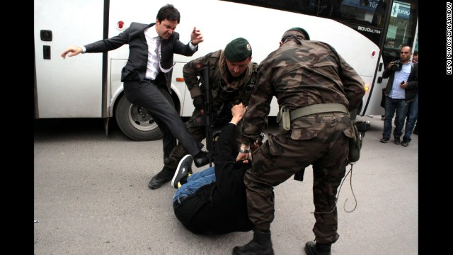 Yusuf Yerkel, an aide to Turkish Prime Minister Recep Tayyip Erdogan, kicks a person who is being wrestled to the ground by two police officers during protests in Soma, Turkey, on Wednesday, May 14.