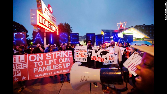 McDonald's employee Connie Ogletree, right, leads a group of fast-food workers and supporters in a chant outside a Krispy Kreme in Atlanta.