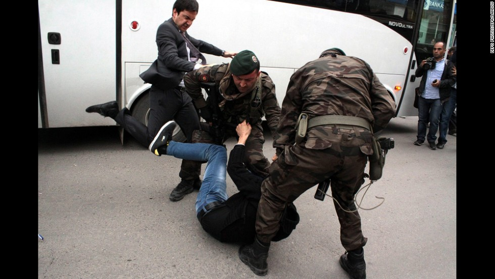 Yusuf Yerkel, an aide to Turkish Prime Minister Recep Tayyip Erdogan, kicks a person who is being wrestled to the ground by two police officers during protests in Soma, Turkey, on Wednesday, May 14. Hundreds of protesters have taken <a href='http://www.cnn.com/2014/05/15/middleeast/gallery/turkey-mine-protests/index.html'>to the streets</a> across Turkey following a <a href='http://www.cnn.com/2014/05/13/europe/gallery/turkey-mine-accident/index.html'>deadly mine fire</a> that occurred near Soma on May 13.