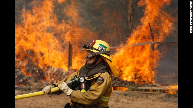 A firefighter pulls a hose on May 15 while battling a wildfire in San Marcos.