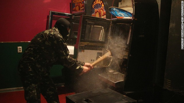 "A member of a ""self-defense"" squad smashes a slot machine with a sledgehammer Monday, May 12, at an illegal club in Slovyansk."