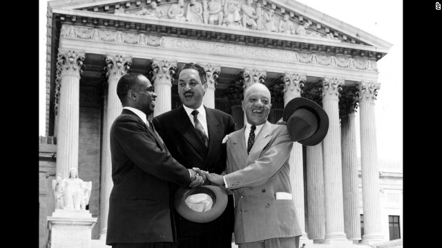 "From left, lawyers George E.C. Hayes, Thurgood Marshall and James M. Nabrit join hands outside the U.S. Supreme Court on May 17, 1954, in celebration of the court's historic ruling. The ruling read in part: ""We conclude that, in the field of public education, the doctrine of 'separate but equal' has no place. Separate educational facilities are inherently unequal."""