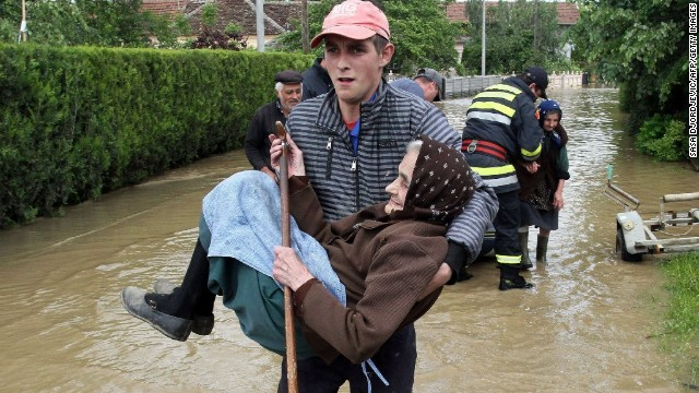 A rescuer carries an elderly woman out of her flooded house in Obrez, Serbia, on Saturday, May 17.