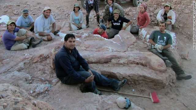 Technicians pose next to fossils that they unearthed.