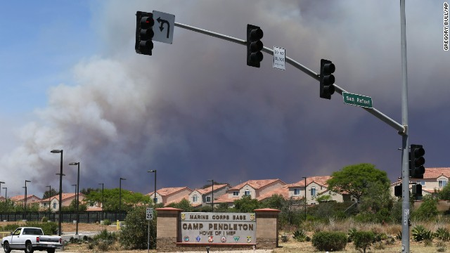 Smoke plumes rise May 16 behind the entrance to Camp Pendleton, a U.S. Marine Corps base.