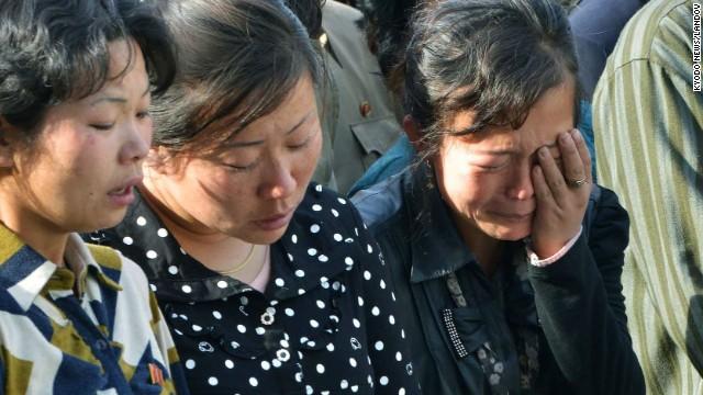 North Korean women listen as the official apologizes.
