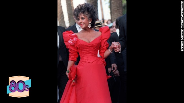 Where in 1957 she wore white, now Elizabeth Taylor attends the 40th Cannes Film Festival in red. The Nolan Miller dress which features iconic shoulder pads has become one of her best known outfits, along with her many wedding dresses.