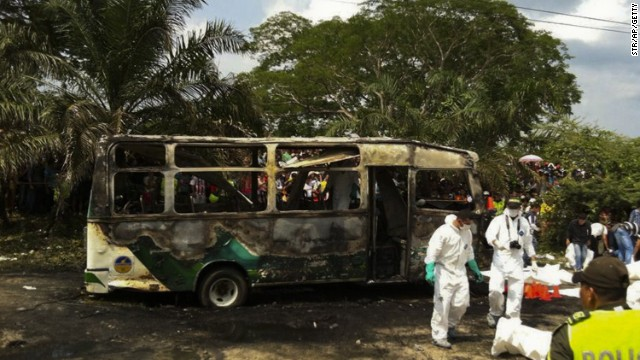 Colombian police stand alongside recovered bodies of children who died in a burned bus in Fundacion, Colombia.