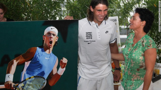 Nadal receives a painting from artist Frederique Lorin as a birthday present. It shows Nadal celebrating after defeating Nicolas Almagro at the French Open in 2008.