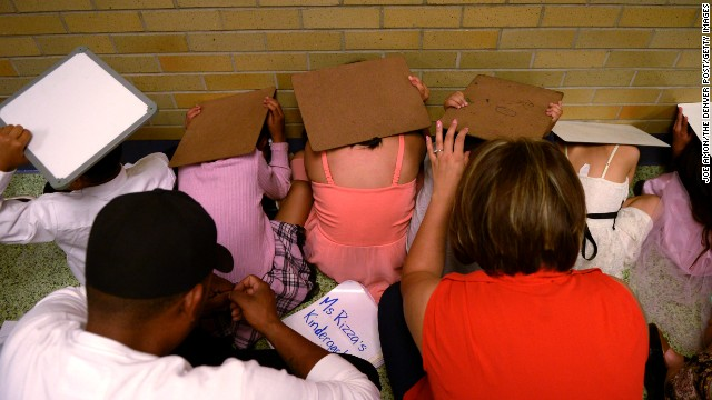 Students and parents huddle deep in the school during a tornado warning at Kenton Elementary in Aurora on May 21.