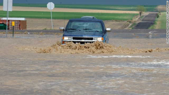 A driver braves the flooded streets east of Denver on May 21.