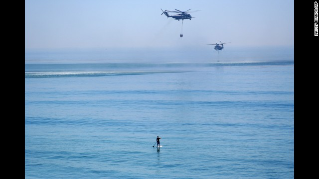 A paddleboarder watches two helicopters grab water from the Pacific Ocean to fight wildfires near Camp Pendleton, California, on May 16.