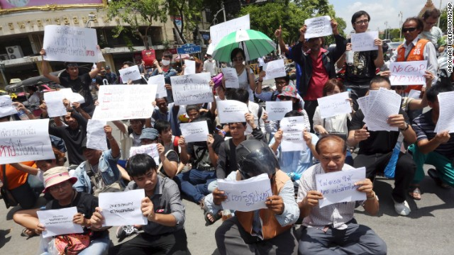 Students and activists hold anti-coup signs during a brief protest near the Democracy Monument in Bangkok on May 23.