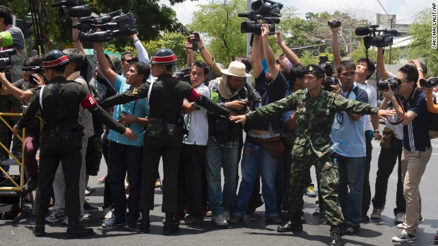 Thai soldiers and military police try to block media as Yingluck arrives at a military compound on May 23.