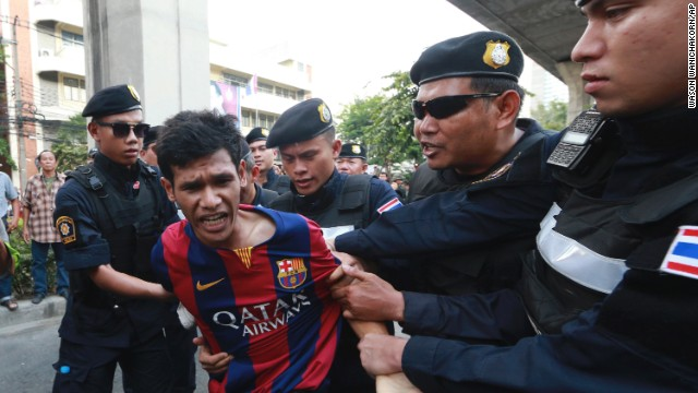 An anti-coup protester is detained by Thai police officers during a protest in Bangkok on Saturday, May 24.