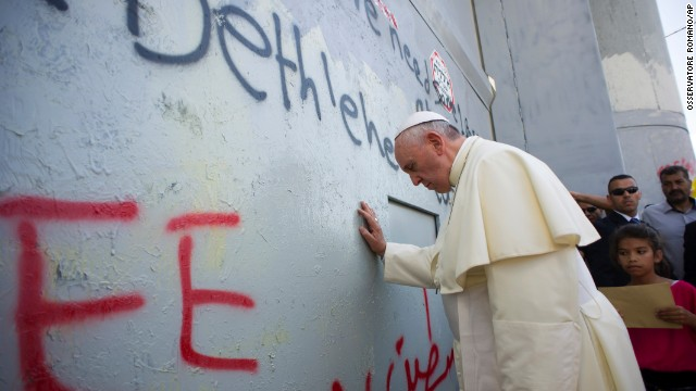 Francis touches the wall that divides Israel from the West Bank on his way to celebrate a Mass in Bethlehem on May 25.
