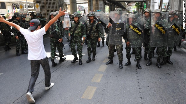 A protester confronts soldiers in riot gear during an anti-coup rally Sunday, May 25, in Bangkok.