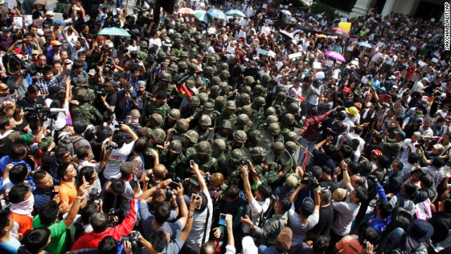 Thai soldiers are surrounded by anti-coup protesters on May 25 during a demonstration in Bangkok.