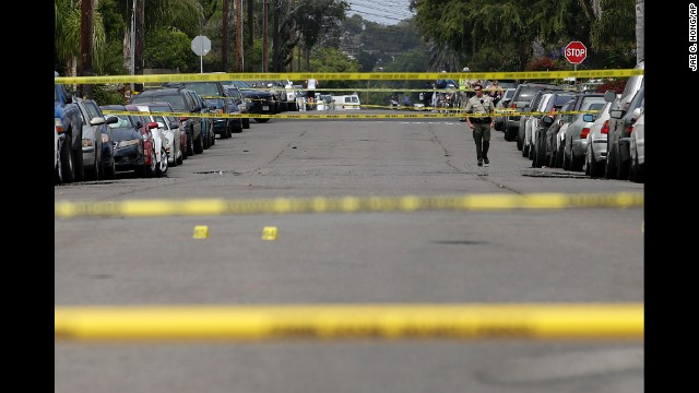 A Santa Barbara County deputy sheriff walks along the street May 24 near a shooting scene in Isla Vista.