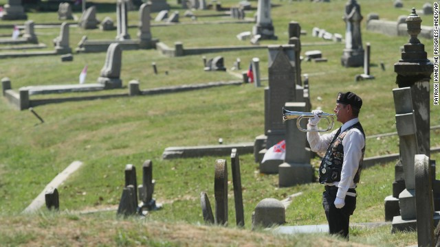 Robert Becker performs taps during a ceremony May 26 at Blandford Cemetery in Petersburg, Virginia.