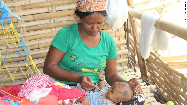 A three-month-old baby is fed by her aunt in the shelter.