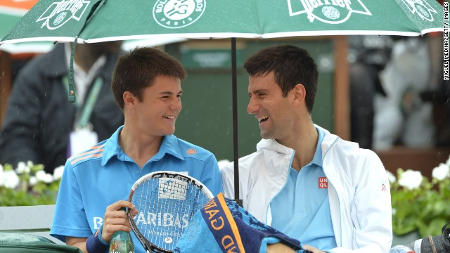 Novak Djokovic shares a moment with a ball boy during a break in play at the French Open in Paris. He went on to beat <!-- --> </br>Joao Sousa in straight sets in a match interrupted by the rain.