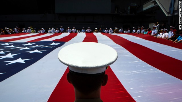 Members of the military unfurl an American flag during a wreath-laying ceremony at the Intrepid Sea, Air & Space Museum in New York on Monday, May 26.