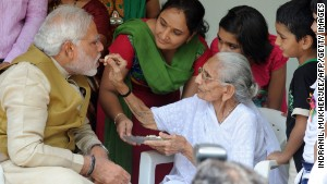 The image said to have moved Sharif\'s mother: Modi\'s mother feeding him sweets on May 16, 2014.