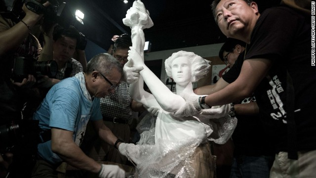 Today, Hong Kong is the only Chinese territory where commemoration of the June 4 crackdown is allowed. Here, pro-democracy legislator Lee Cheuk-yan (left) unwraps a replica of the Goddess of Democracy at Hong Kong's June 4 Museum that opened on April 24, 2014.
