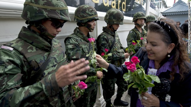 Thai soldiers receive roses from coup supporters at a military base in Bangkok on May 27. Since taking power, military authorities have summoned -- and in some cases detained -- scores of political officials and other prominent figures.