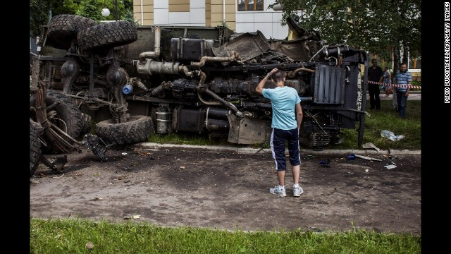 A man stands in front of a truck that was bombed by Ukrainian soldiers during clashes with armed rebels Tuesday, May 27, in Donetsk.