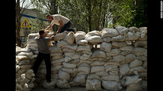 People pile up sandbags to set up a shooting position on the road leading from the Donetsk airport on May 27.